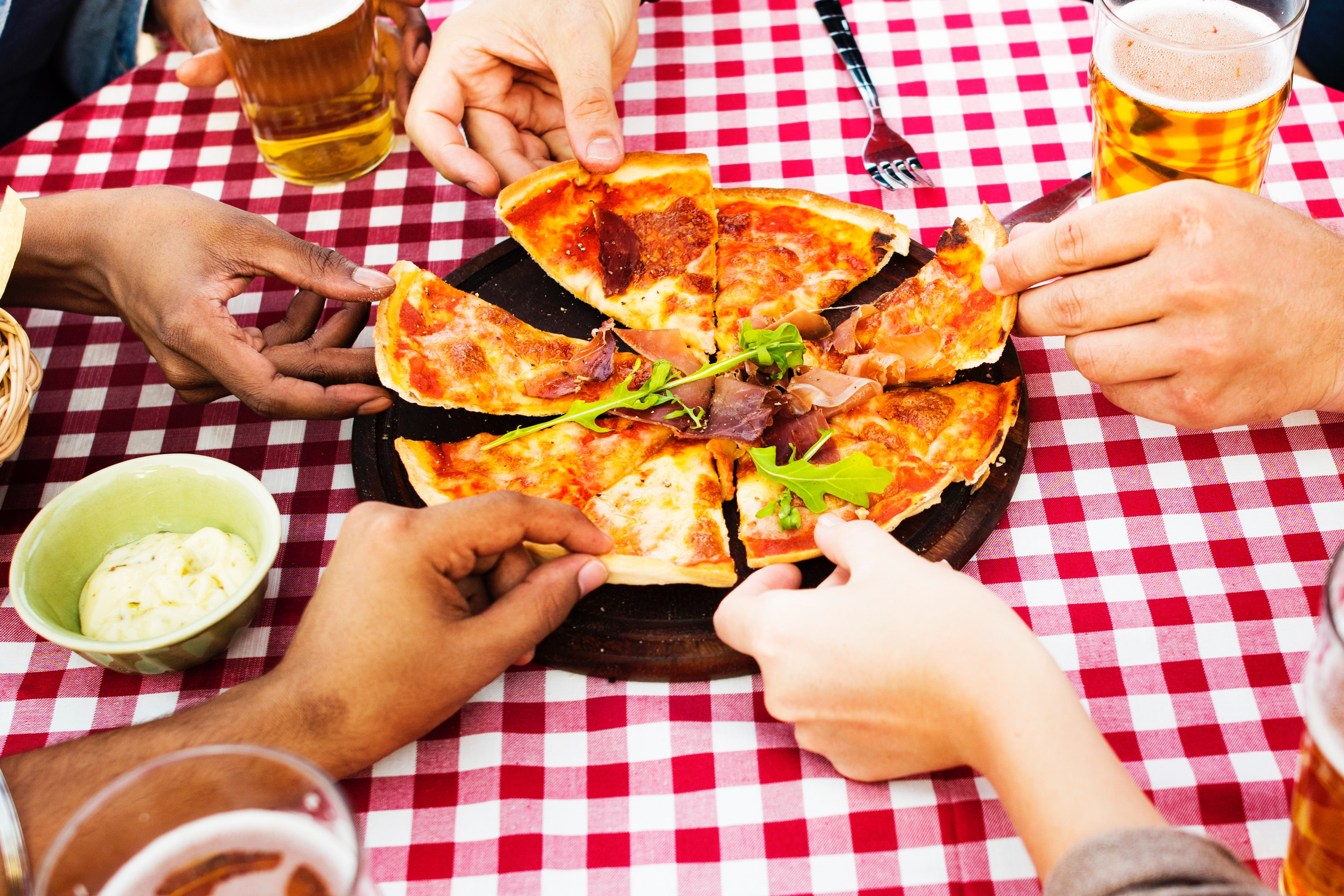 people sharing a pizza with beer