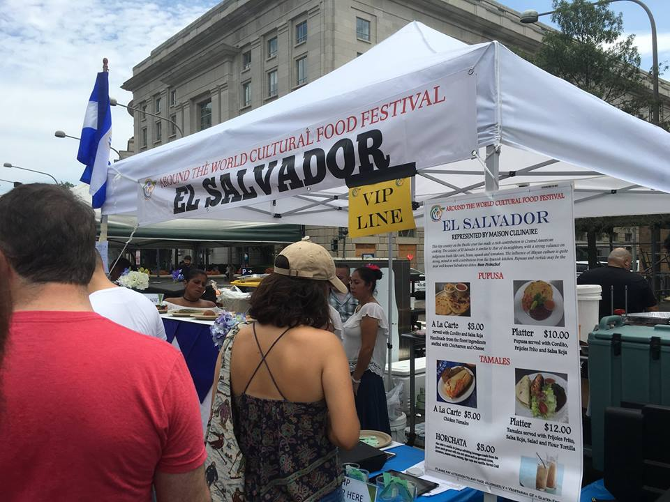 visitors browsing salvadoran stand at festival
