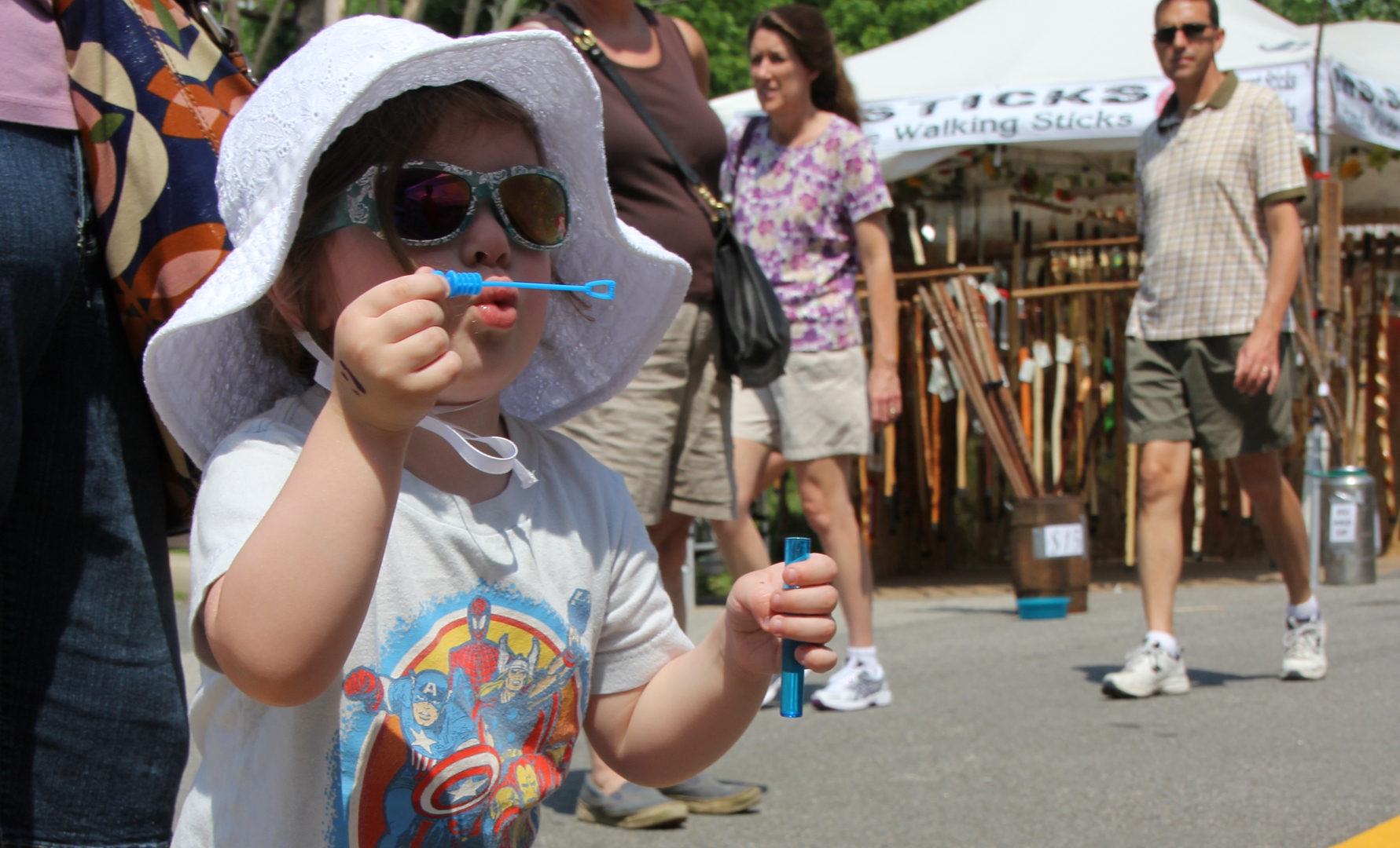 child blowing bubbles at arts and crafts festival