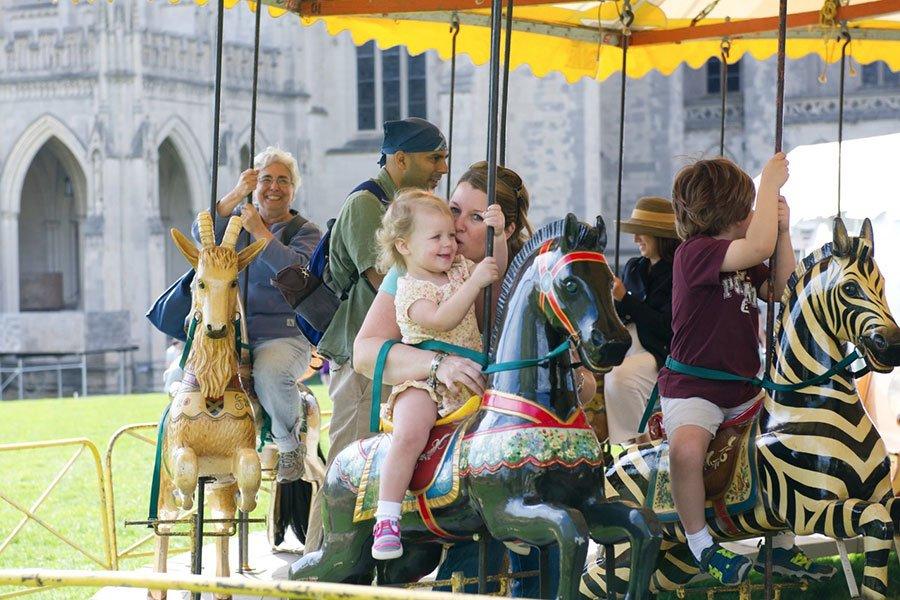 People riding carousel, courtesy of washington national cathedral