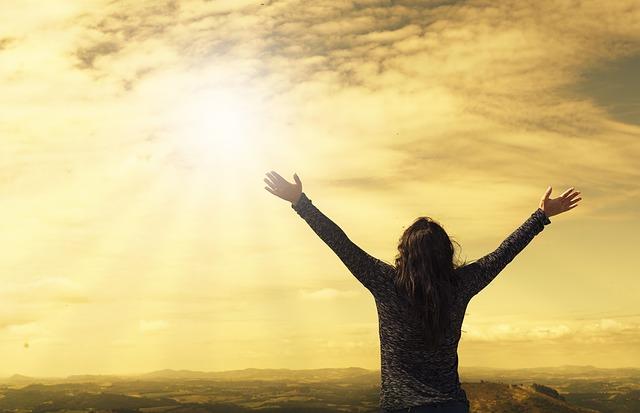 woman lifting hands towards sky
