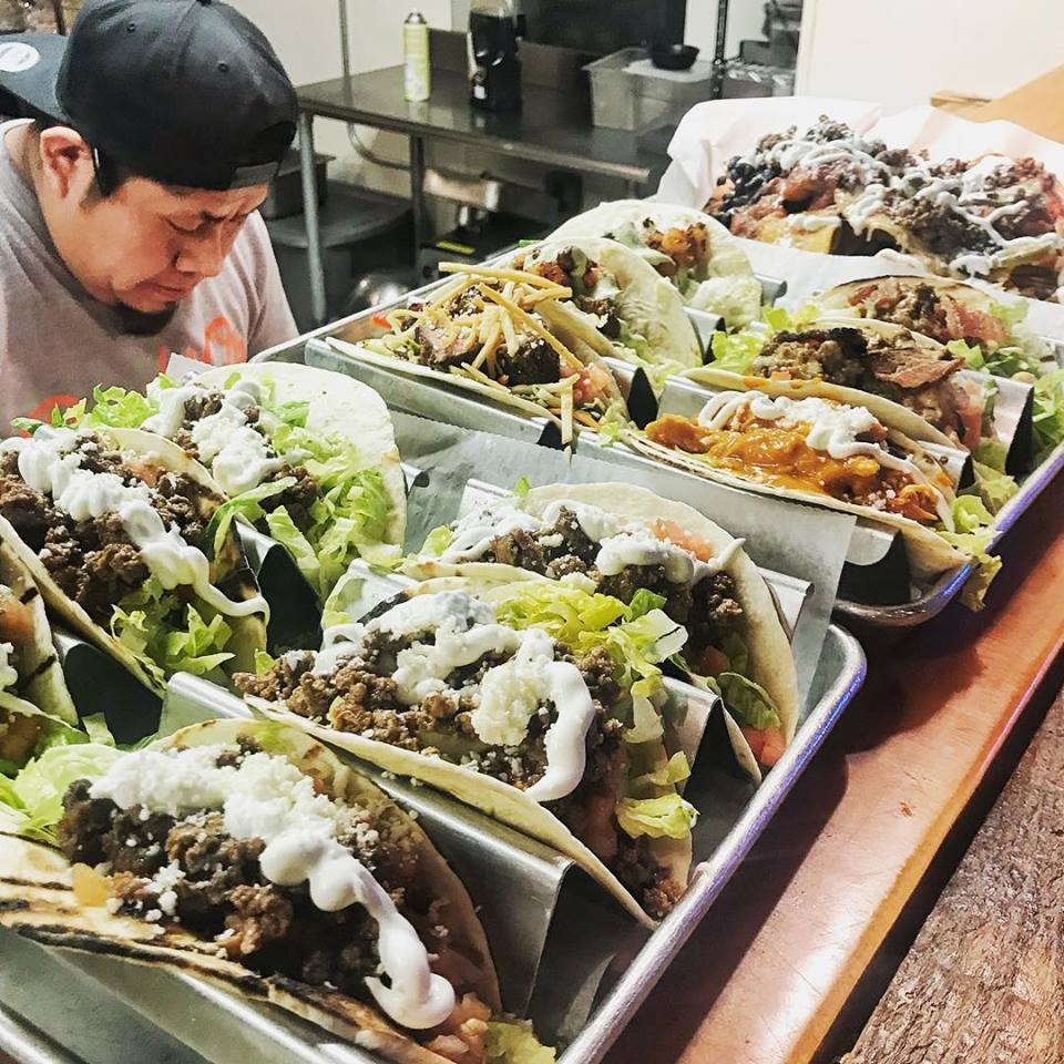 cook behind counter with tacos at banditos